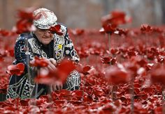 Harry Mayhead, Pearly King of Bow Bells who served in Egypt and France for the Royal Army Service Corp. in WWII, plants poppies at the Tower of London, Friday, Sept. 19, 2014. 'Blood Swept Lands and Seas of Red' is the evolving art installation at the tower, and 888,246 poppies will be planted in the moat by volunteers with the last poppy being planted on Nov. 11 2014. Each poppy represents a British or Colonial fatality in the First World War. (AP Photo/Kirsty Wigglesworth)