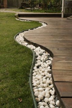 Here's a curvy ground level deck with landscaping stones around the edges.
