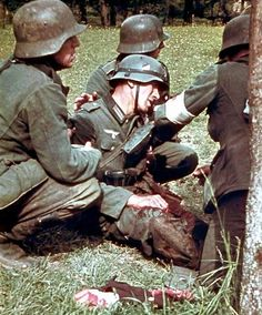 Wounded german soldier and a dismembered limb in foreground. Eastern front. WW 2. Rare color photo. The horrors of war.