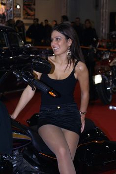 Pretty promo model in a miniskirt poses precariously on a bike!
