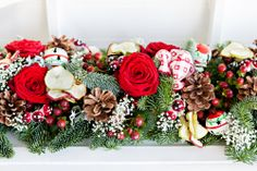 #christmas garland created from seasonal foilage, red Naomi roses. fir cones and red berries. A sprinkling of gypsophilia gives the impression of freshly fallen snow.