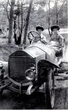This postcard shows two Hangyoku (Young Geisha) sitting in an early Automobile. The car is a Colibri (Hummingbird) manufactured by the Norddeutsche Automobil-Werke (North German Auto Works) between 1908 and 1912. by MyohoDane