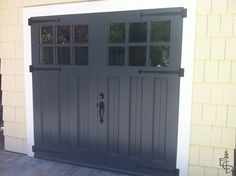Black carriage doors on yellow house with white trim, via Evergreen Carriage Doors