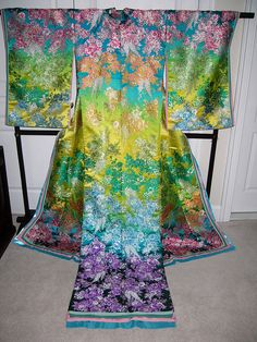 Modern wedding kimono    Modern reworking of the wedding kimono with short sleeves and a train. This design is known as mai curren and is inspired by Chinese robes. Mai curren uchikake tend to be very colourful; this one has blossom clusters in rainbow hues.