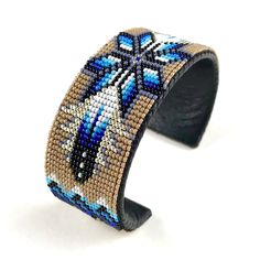 This bold cuff was made by Navajo artist Iris Nathaniel and features a central geometric design surrounded by feathers. The large cuff was made. Native Beading Patterns, Beadwork Designs, Native Beadwork, Native American Beadwork, Beaded Jewelry Patterns, Beaded Braclets, Bead Loom Bracelets, Woven Bracelets, Loom Bracelet Patterns