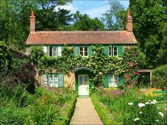 A beautiful cottage with red brick roof, chimneys, large garde, winding path and shutters on the windows :)