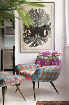 A parede do cantinho de leitura foi decorada com um quadro de cores neutras. A poltrona cheia de estampas com cores vivas dá vida ao espaço e complementa a decoração com muito charme!