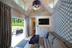 Amazing pool house features vaulted ceiling dotted with navy drum chandelier illuminating accent wall clad in white and blue geometric wallpaper framing gray stripe sofa with tufted seat cushions facing folding doors dressed in Greek key curtains across from a navy vinyl bench situated across from a small bathroom beside a built-in cabinets adorned with flat screen TV.