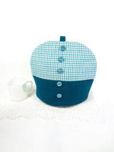 Here is a smart tea cozy hand crafted from solid teal and turquoise, white and grey hounds tooth wool. The design is inspired by 1960s fashion-