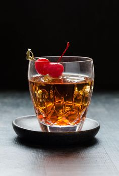 Straight on image of perfect manhattan cocktail recipe in low ball glass with ice and cherries for garnish.