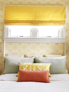Yellow, persimmon & gray color combo - White & yellow wallpaper, yellow linen roman shade, glossy white faux bamboo bed, gray pillows with yellow piping, yellow ikat pillow and persimmon pillow.
