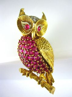 The owl features a ruby breast and eyes.  The top of his head is pave set with 18 round diamonds weighing 0.55 carats total. He has very detailed engraved 18k yellow gold feathers and is perched on an 18k yellow gold branch. Circa 1970's.2 1/4 inches in length. $ 4,200.00