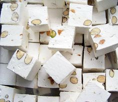 Nougat is a variety of similar traditional confectioneries made with sugar and/or honey,roasted nuts (almonds,walnuts,pistachios,hazelnuts,and recently macadamia nuts are common),whipped egg whites,and sometimes chopped candied fruit. The consistency of nougat can range from soft and chewy to hard and crunchy depending on its composition,and it is used in a variety of candy bars and chocolates.