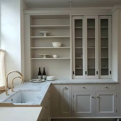 Neutral white kitchen from Swedish kitchen manufacture Kvanum. Marble countertops, brass fixtures.