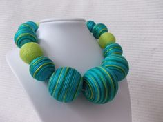 Green-Turquoise striped textile necklace This marvellous necklace is a great fashion accessory for any woman. It features green- turquoise colour. Combination of the natural and soft colors. Different sizes of cotton balls are wound with a silk thread. The textile beads are hanging on light green silk ribbon. https://www.etsy.com/listing/604540953/green-turquoise-striped-textile?ref=shop_home_active_1