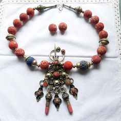 by Anne Marie of BeadArtAustria   Necklace created around an old silver enamelled Berber fibula, combined with lapis, sterling silver and large sponge coral beads   335$