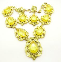 """Huge yellow Czech Glass Statement Necklace. Set in non-plated brass. Measures 17"""" and also has a 2 1/2"""" extension chain. The larges drop measures 2 14"""" by 1 3/4"""" The matching clip earrings measure 3 1/4"""" by 1 1/2"""" . Very good condition."""