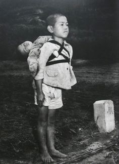 Japanese orphan, bringing his dead brother to a cremation pyre, Nagasaki,  1945