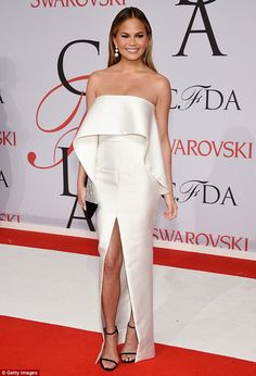 White hot! Chrissy Teigen put on a leggy display in a strapless white gown slashed to the ...
