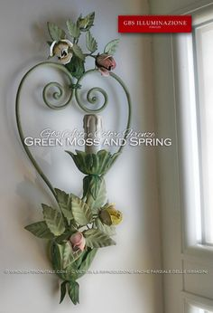 Romantic wall light sconce with forged iron heart and small bouquets of roses and buds