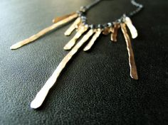 A hammered gold fringe necklace with a blackened silver chain. Very cool and dramatic.