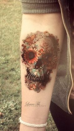 floral skull watercolor tattoo on forearm - butterfly, sunflower