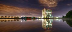 FERMI NATIONAL ACCELERATOR LABORATORY'S WILSON HALL AND REFLECTION IN SWAN LAKE AT NIGHT via ENERGY.GOV