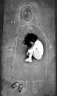 An Iraqi girl in an orphanage - missing her mother, she drew her and fell asleep inside the drawing of her .