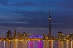 The dramatic cityscape of downtown Toronto is best seen from the Toronto Islands where reflections of the city's bright lights are cast on the surface of Lake Ontario. The Toronto Islands are a short ferry ride from the city centre.