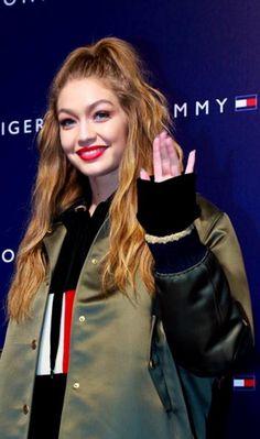 Who made  Gigi Hadid's black sweater and green jacket?