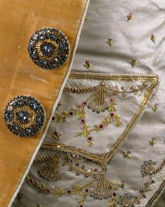 Detail embroidery and buttons, suit, France, ca. Saffron coloured velvet with detachable cuffs of cream silk satin, embroidered with flower sprays and exotic trees adn flowers; waistcoat: cream silk satin with matching embroidery.