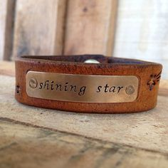 """Starburst"" is perfect for the performer, the one who sees themselves as a star! Or better yet, for the astronomy buff who loves star gazing! Starburst is 3/4"" wide with several shooting stars careening toward a rectangular word plate in an antique brass finish. It's leather comes in Autumn Tan. To customize, choose a font and your word/phrase. (To order click link in bio) The Starburst is $30. https://www.facebook.com/Catz16Designs"