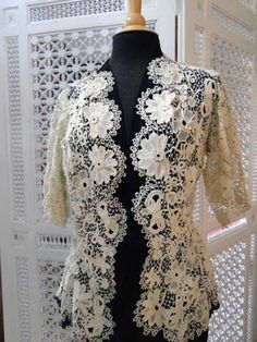 CIRCA 1900,LOVELY IRISH CROCHET JACKET.A very wearable Irish Crochet jacket with a slight flare at the back. Large bold ornate flowers have three-dimensional raised decorations and the jacket has scalloping on all edges.A couple of minor openings, otherwise very good condition.Mannequin is a size 8.(Item #LCE14)