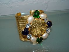 Chanel 1980's Spectacular Gold Cuff with Crystal, Glass, and Pearl Stone Detail Set About an Enormous Logo Coin