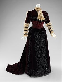 1890 Beaded burgundy silk velvet reception dress with linen sleeves and jabot, American, 1890. This dress is in keeping with the interest in historical revivals popular in the 19th century. The long puffed sleeves refer to both Elizabethan and early 19th-century styles. The one-piece construction indicates it was probably intended for formal reception at home.