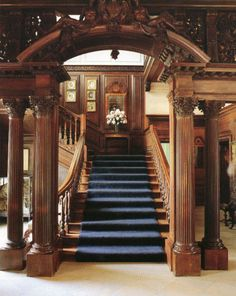 Westbury House, Old Westbury, Long Island, New York. The stairway is partially separated from the main entry hall by a carved wooden screen. A segmental pediment topped by angels crowns the approach to the stairway.