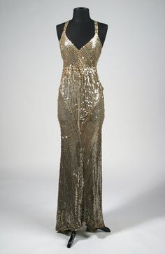 """A long silver sequin and nude chiffon """"V-style"""" gown with 1 inch straps designed by Edith Head for an unknown production. Hand sewn label inside reading """"BY 7."""""""