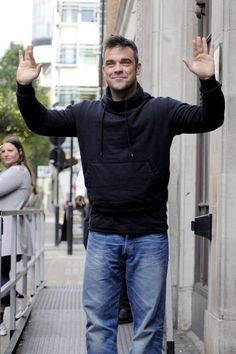 Robbie Williams Photo - English singer Robbie Williams greets fans while leaving BBC Radio One in London
