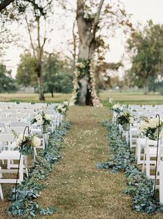 This outdoor wedding ceremony decor consisted of greenery garlands of eucalytpus to line the aisle, along with a floral backdrop   decorating a tree as the altar. | Stephanee & Johnathan's Real Wedding by Mariel Hannah Photography from mywedding Magazine #myweddingmag