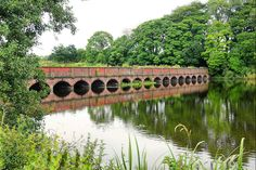Multi arched bridge over Carr Mill Dam in St Helens, Merseyside, England....Carr Mill Dam is also the location of St. Helens' only ancient woodland running alongside the railway line.