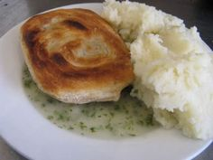 a plate of pie and mash with parsley liquor