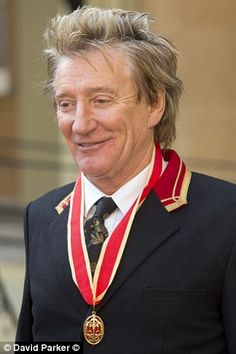 Delighted: The rocker posed for photos after receiving his honour from the Duke of Cambridge