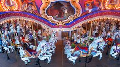 Rows of majestic horses under an inner rounding board with a hand-painted vignette of Cinderella