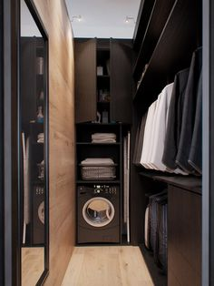 A modern and masculine walk-in closet, complete with laundry machine! | Design by INT2 architecture