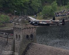 A Lancaster bomber aircraft from the Battle of Britain Memorial Flight (BBMF) soars over the Derwent Valley Dam in Derbyshire. The famous 'Dambusters' of the RAF's 617 Squadron trained in this valley during the Second World War for their mission.