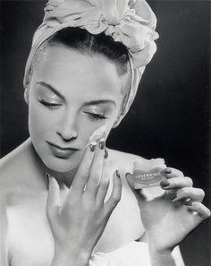 Glamorous woman applying skin cream, 1945-1955.