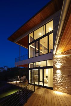 Lake Travis Residence by Hsu Office of Architecture    Description from the architects:    Built atop a sloping site off Lake Travis, this two story custom residence utilizes a bisecting plan to offer flexible open space and respond to the grade of the site.  Natural materials such as wood siding, stacked ledge stone and stucco are used to tie into the landscape.  A large butterfly roof and expansive windows capture views and embrace the surrounding vista.