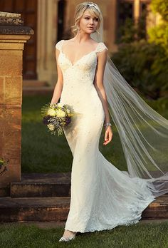 Brides: Essense of Australia. See more details from Essense of AustraliaSheath bridal gown features cap sleeves, a stunning V-neckline and sparkling diamanté accents throughout. The lace flows past the under-dress into an elegant train.