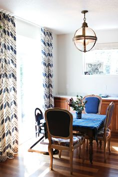 Indigos and blues are Deepali's favorite hues.  The curtains in the dining room are made by her company, the table and chairs were Craigslist scores, and the light fixture was found during her many travels.
