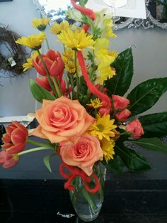 Tulips,  daisies, standard,  and spray roses accented with wool wire.